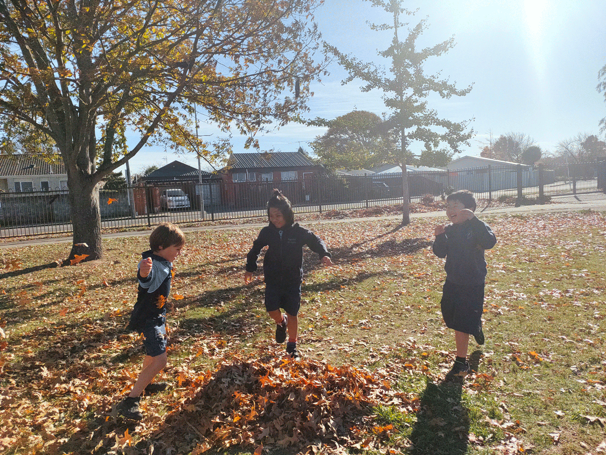 3 Papanui Primary Students playing with leaves