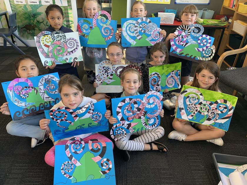 Papanui Primary students holding up their artwork