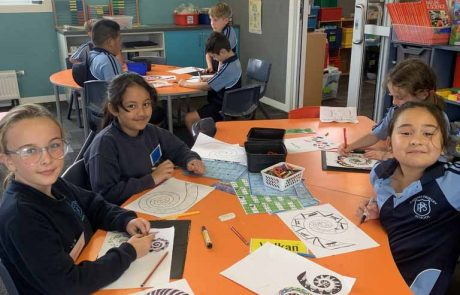 Papanui Primary students seated at an orange desk doing art